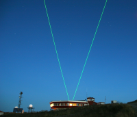 Fig. 1:ALOMAR observatory and laser beams of the ALOMAR RMR-lidar during operation with tilted telescopes (courtesy, J. Fiedler)
